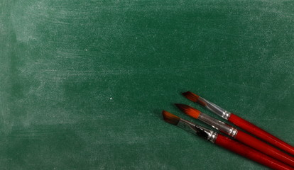 Paintbrushes on chalkboard, blackboard and texture