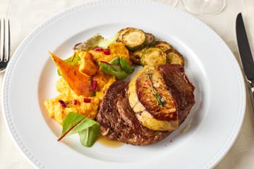 Rib-eye steak with duck liver, roast batata and zucchini
