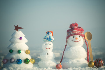 Snowmen with smiley faces in hats on winter day