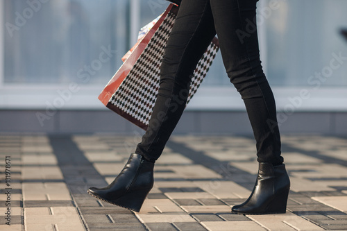 Sexy Woman Legs In Black Platform Shoes And Black Jeans With Shopping Bags Walking In The