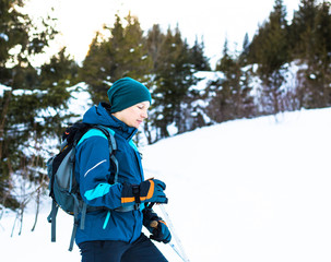 Young happy traveler hiking in beautiful mountains. Fantastic winter landscape.
