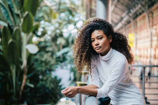 Portrait of young woman with curly afro hair standing against fence in shopping mall.