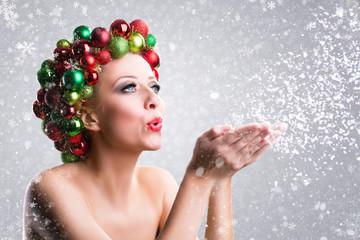 Weihnachtlich geschmückte Frau pustet Schnee