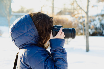Young woman taking photo outdoor on winter