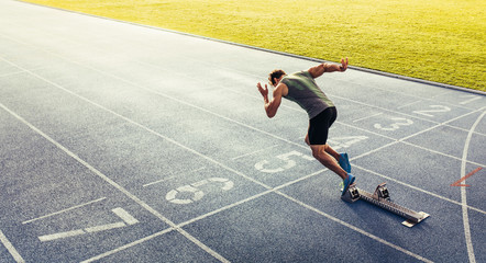 Sprinter taking off from starting block on running track Wall mural