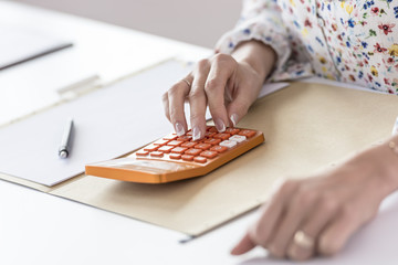 Businesswoman using orange calculator in the office as she sits at her desk, close up view of her hands.