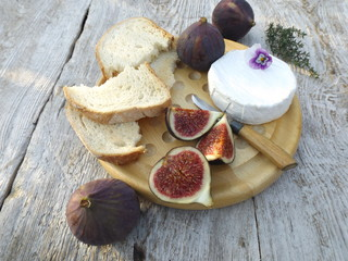 Cheeseboard. Brie cheese, bread and figs on a round wooden board.