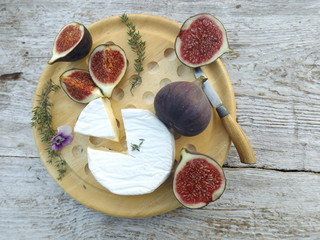 Cheeseboard. Brie cheese and figs on a round wooden board