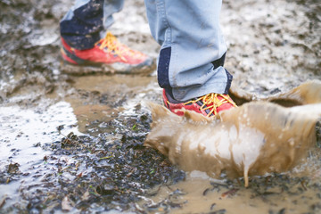 Detail of trekking boots in a mud. Muddy hiking boots and splash of water. Man splashing in muddy and water in the countryside.