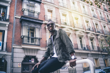 Handsome black man poses in city.