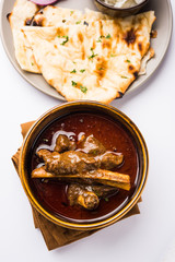 Mutton Masala Or Masala Gosht or indian lamb rogan josh with some seasoning, served with Naan or Roti, selective focus