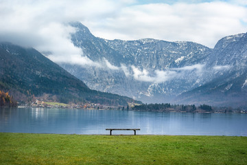 Austrian Alps and a bench on lakeside - Beautiful scenery with the majestic Northern Limestone Alps, the Hallstatter lake and a wooden bench on its shore, in the famous Hallstatt town, in Austria.