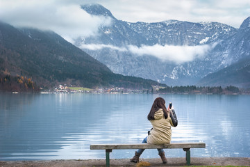 Woman on lakeshore using her phone - Woman sitting on a wooden bench, on the shores of the Hallstatter lake, using smartphone to photograph the Austrian Dachstein mountains, in Hallstatt, Austria.