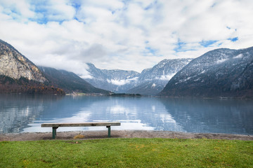 Wooden bench on alpine lake shore - Holiday locations theme image with the Dachstein mountains reflected in the Hallstatter lake water and a wooden bench placed on its shore, in Hallstatt, Austria.