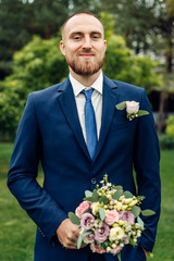 groom in a suit with a wedding bouquet is standing alone waiting for his wife in the autumn garden after the wedding ceremony