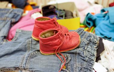 Gebrauchte rote Schuhe für Kinder in einem Second Hand Laden