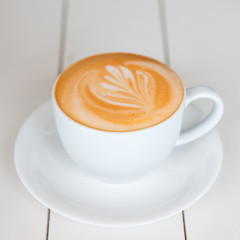 Top view of Latte coffee or cappuccino coffee in white cup with latte art on white wooden table.