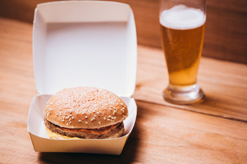 Fresh and juicy hamburger and beer on wooden background