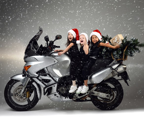 Young happy girls kids ride a motorcycle bike in santa hat and christmas tree