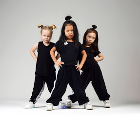 Group of three young girl kids hip hop dancers on gray