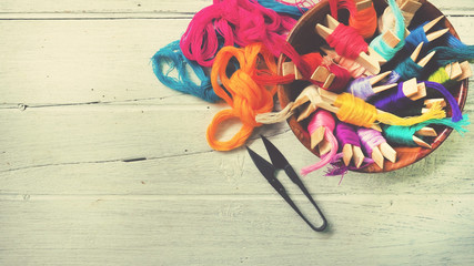 Colorful thread on wood workplace background, selective focus and vintage color tone process