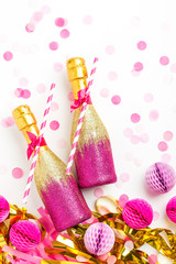 Pink and Gold Mini bottles of champagne with confetti and tinsel. Flat lay. New year celebration or wedding concept theme