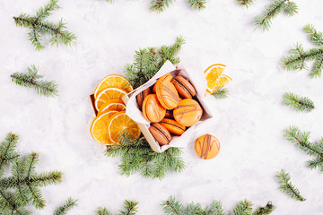 Gift box with oranges; macaroons and fir branches on a gray background. Flat lay; top view