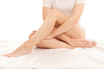 Long and slim woman legs on white sheets in bed isolated over white background