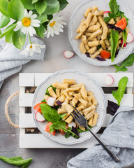 Homemade gnocchi. A traditional Italian dish. Gnocchi with oil of spices and a salad of fresh vegetables and herbs: radish, tomato, arugula, basil. On a light concrete background  Flat lay, top view