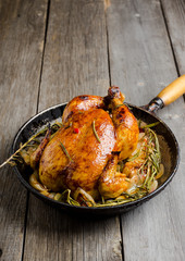 Roasted chicken in pan on the rustic wooden background. Selective focus.
