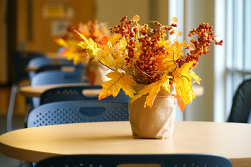 Close up on autumn decoration leaf and flower in vase on the table