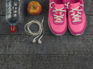 Beautiful pink sneakers, headphones, water and apples on a wooden black floor. View from above.