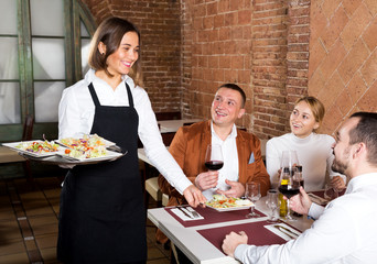 Waitress placing order in front of guests