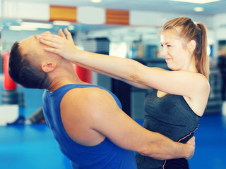 Cheerful woman is fighting with trainer
