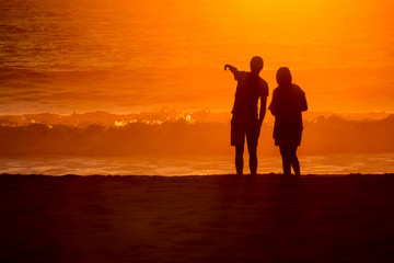 silhouetted couple loverlooking sunset washed waves