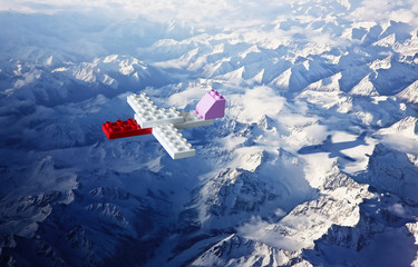 Plastic building blocks with aeroplane shadow , top angle view ice mountain landscape . Creative and ideal concept .