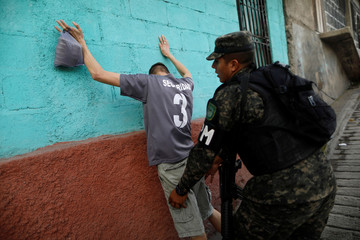 A soldier frisks a civilian as part of security measures for the November 26 presidential election in Tegucigalpa