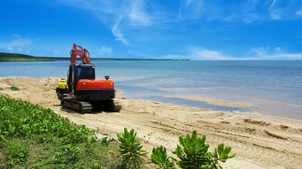 Excavator moving beach sand after erosion