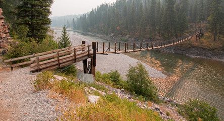 Suspension Plank and Wire Bridge over the Flathead River at the Spotted Bear Ranger Station / Campground in the Bob Marshall Wilderness area during the 2017 fall fires in Montana United States
