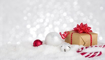 Christmas gift box and decoration in snow against bokeh background