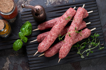 Above view of raw cevapi or cevapcici sausages on wooden skewers, studio shot