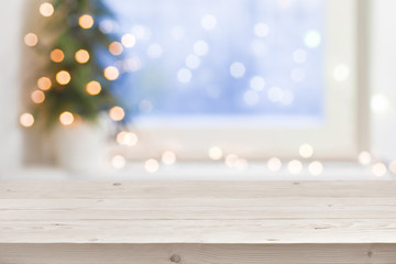 Empty wooden table in front of blurred winter holiday background