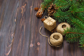 christmas present box and fir branches with cinnamon and anise on rustic wooden background. flat lay. seasonal greetings concept. winter holidays