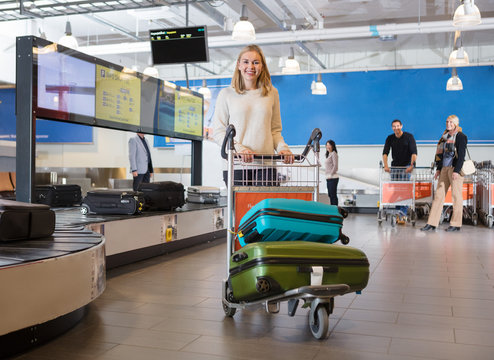 Young Woman With Luggage In Cart At Airport