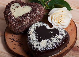 Chocolate baked in the shape of heart and beautiful light rose flower. Valentine's Day.