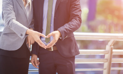 Hand of Businessman and Businesswoman in heart shape,feeling love in office