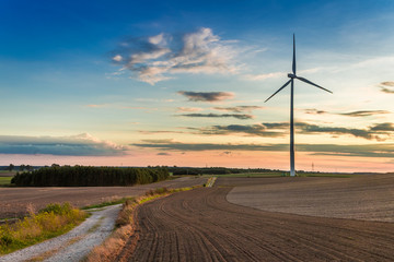 Amazing sunset at brown field with wind turbine in autumn