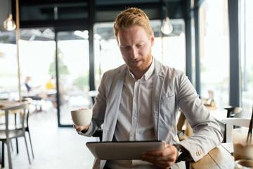Busy businessman enjoying coffee while online