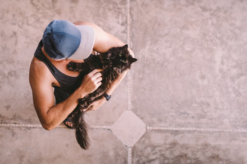 Young male adult carrying cute cat on his arms