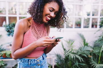 Young happy african woman texting message on phone Fototapete